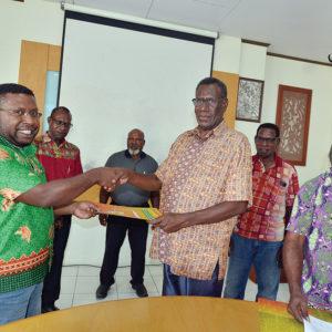 Direktur LEMASA, Odizeus Beanal (kiri) menerima berkas perjanjian kerja sama dari Ketua BAdan Pengurus LPMAK, Robertus Waropea.
