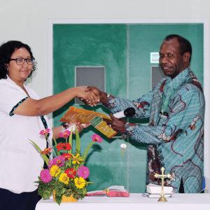 Sekretaris Eksekutif LPMAK, Abraham Timang menyerahkan berkas serah terima Bangsal Santa Clara kepada Plt. Direktur RSMM, dr. Theresia Nina di Timika, Senin (15/4). (Etty Wellerubun/LPMAK)