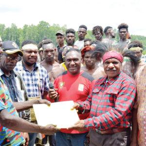 Ketua Badan Pengurus LPMAK, Elminus Mom menyerahkan berkas usai penandatangan serah terima hibah kapal ikan dari Biro Ekonomi Suku Kamoro kepada kelompok Nelayan Mandiri.