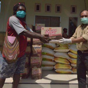 Wakil Direktur Bidang Evaluasi dan Monitoring YPMAK, Yohan Wambrauw menyerahkan langsung bantuan bahan makanan kepada masyarakat di Petrosea, Kelurahan Timika Indah, Distrik Mimika Baru.