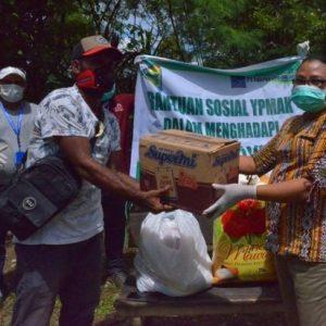 Sekertaris YPMAK Johanna Julianan Saidui menyerahkan bahan makanan kepada Kepala Kampung Utikini Dua Marinus Kogoya