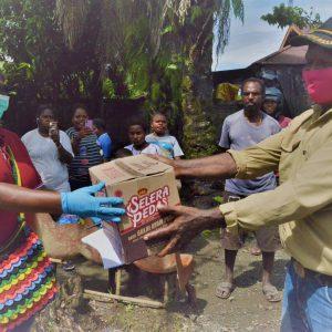 Karyawan YPMAK Marina Beanal menyerahkan bahan makanan kepada masyarakat.
